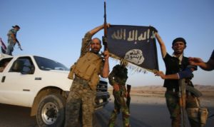 Iraqi Shiite militia fighters hold the Islamic State flag as they celebrate after breaking the siege of Amerli by Islamic State militants, September 1, 2014. Picture taken on September 1, 2014. REUTERS/Youssef Boudlal (IRAQ - Tags: CIVIL UNREST POLITICS MILITARY TPX IMAGES OF THE DAY) - RTR44N6G